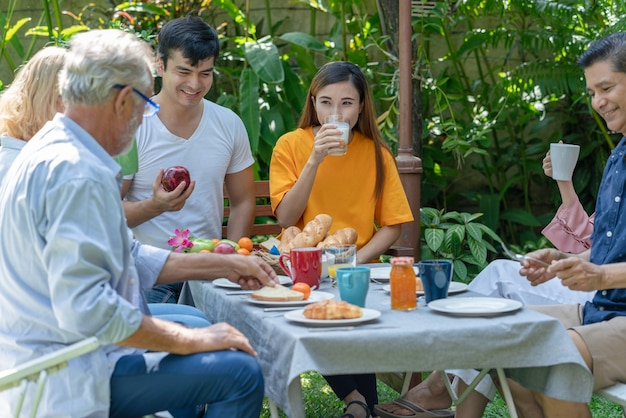 Happy family have fun eating breakfast together at home garden in the morning