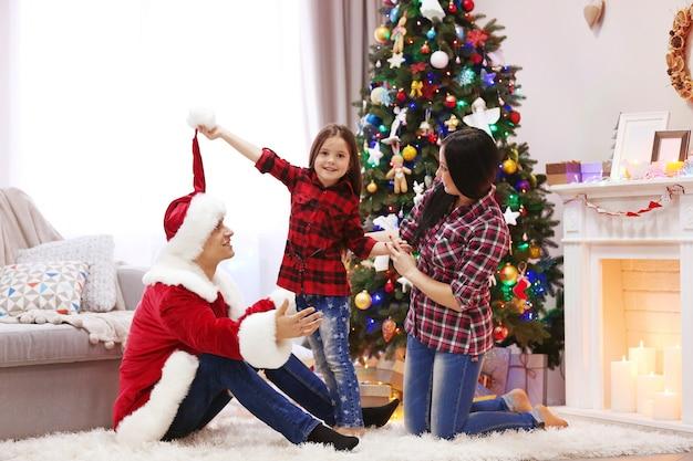 幸せな家族は、装飾されたクリスマスルームで楽しんでください