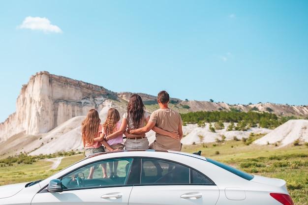 幸せな家族は彼らの車の旅で美しい自然の中で休暇を楽しんでいます