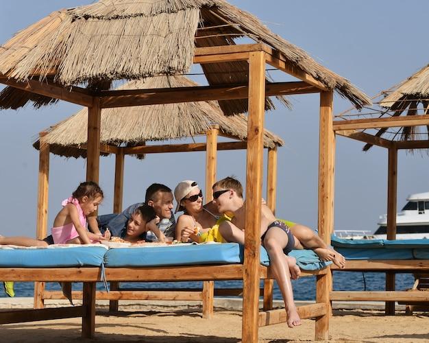 ビーチで昼食をとっている幸せな家族
