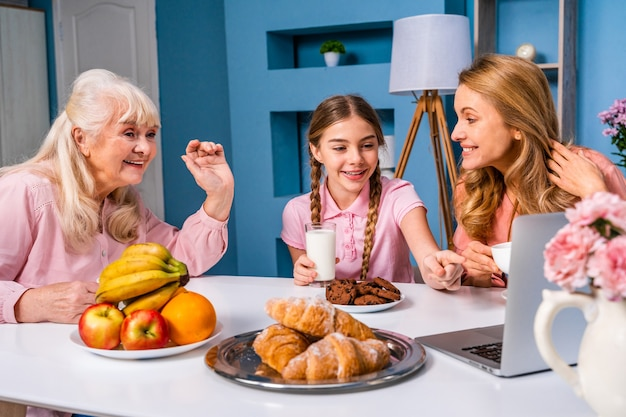 Happy family having breakfast in the morning at home while having a videocall