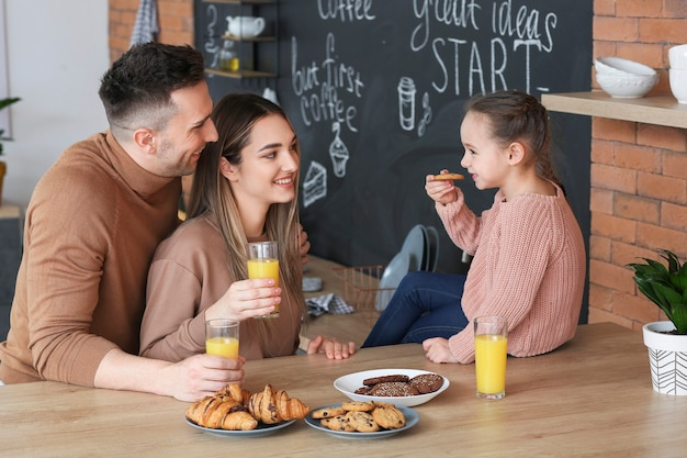 Happy family having breakfast together in kitchen