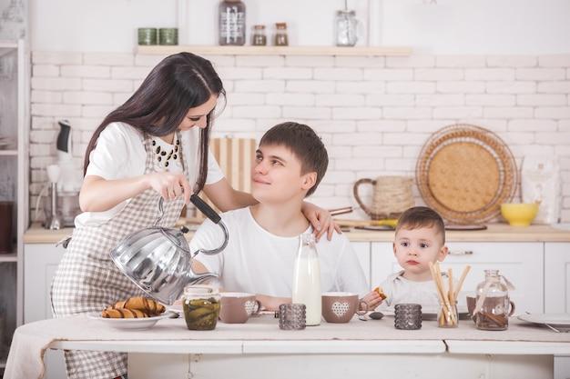 一緒に朝食を食べて幸せな家族。キッチンのテーブルで食べる若い家族。ママ、パパ、小さな赤ちゃんが食べています。
