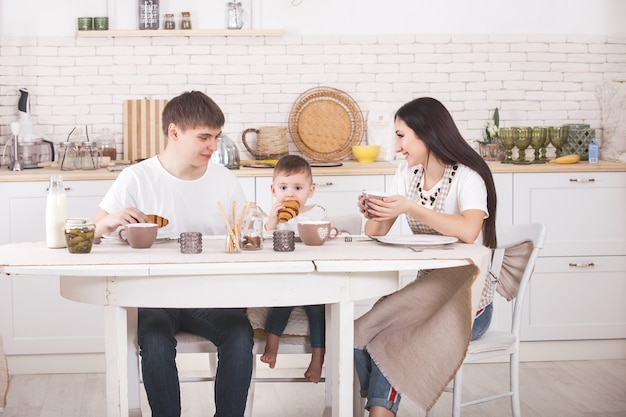 Happy family having breakfast together. young family eating at the table on the kitchen. mom, dad and little baby eating.