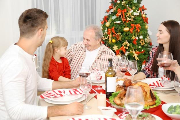 リビングルームでクリスマスディナーを持っている幸せな家族