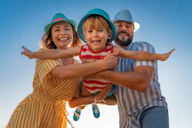 青い空を楽しんで幸せな家族。夏休みの母、父、娘、息子