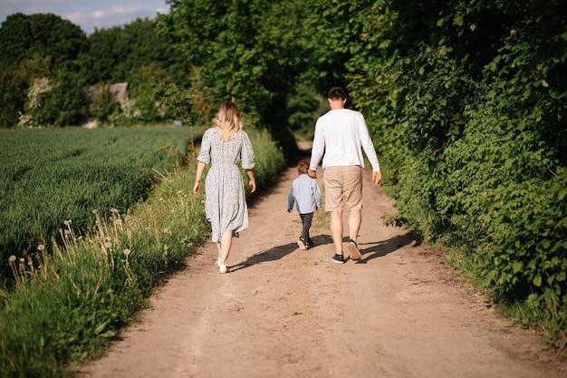 Счастливая семья веселится и гуляет по проселочной дороге, держась за руку, фото вид сзади