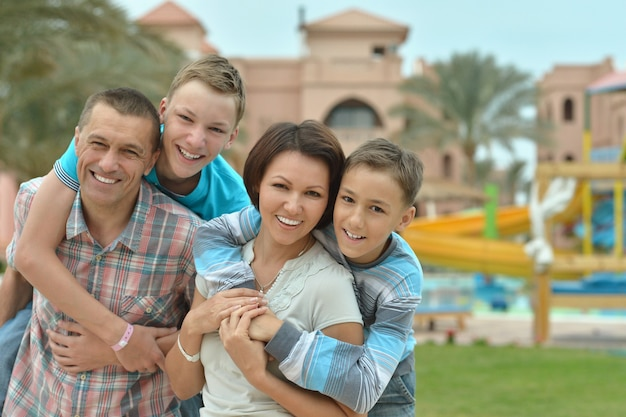 Счастливая семья весело на тропическом курорте возле бассейна.