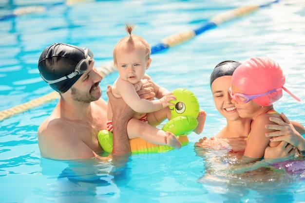 Famiglia felice che si diverte a bordo piscina.
