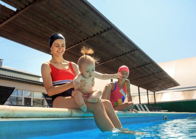 スイミングプールで楽しんで幸せな家族。