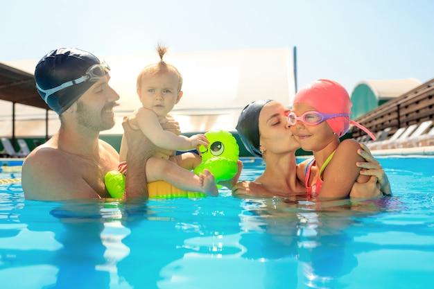 Счастливая семья веселится у бассейна
