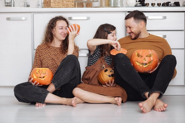 Happy family having fun at home with pumpkins for halloween