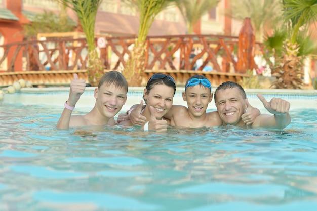 엄지손가락으로 수영장에서 즐거운 시간을 보내는 행복한 가족