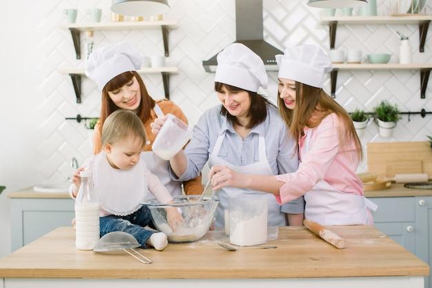 キッチンで楽しんで幸せな家族。祖母と娘たち、小さな女の赤ちゃんが自宅のキッチンで一緒に生地を混練します。幸せな母の日、家族の料理