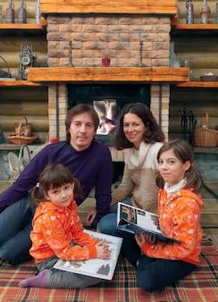 木造住宅の暖炉のそばで楽しんで幸せな家族。冬の週末に本を読む子供を持つ親