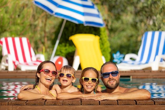 Счастливая семья, весело проводящая время на летних каникулах отец, мать и дети, играющие в бассейне, концепция активного здорового образа жизни Premium Фотографии