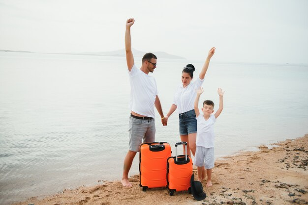 Счастливая семья, весело проводящая время на пляже. летние каникулы и концепция путешествий
