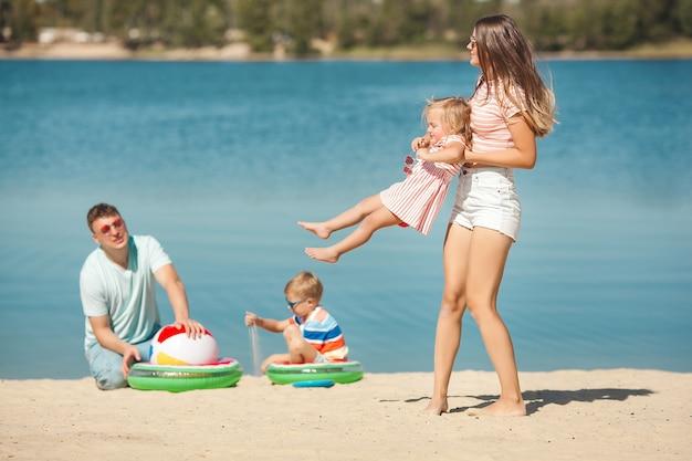 ビーチで楽しんで幸せな家族。