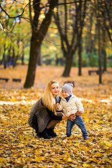 Famiglia felice che ha divertimento all'aperto nel parco di autunno contro foglie sfocate
