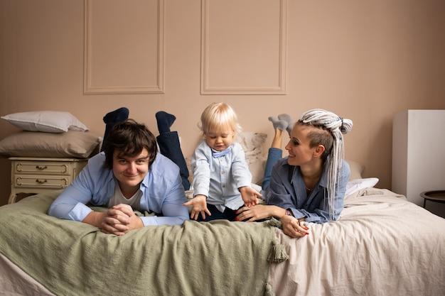 행복한 가족이 집에서 침대에서 즐거운 시간을 보내고