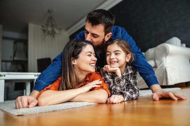 一緒に素晴らしい時間を過ごしている幸せな家族。お父さんがお母さんにキスしながら床に横たわっているお母さんと娘。健康な子供時代。