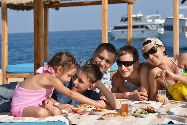 Happy  family having lunch on a beach