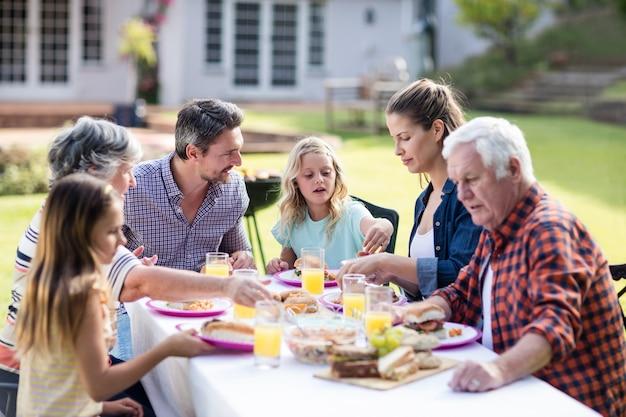 庭で昼食を食べて幸せな家族