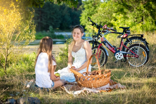 Happy family having picnic by the river. smiling mother and daughter looking at each other