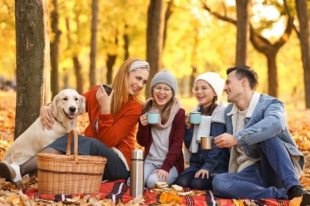 秋の公園でピクニックをしている幸せな家族