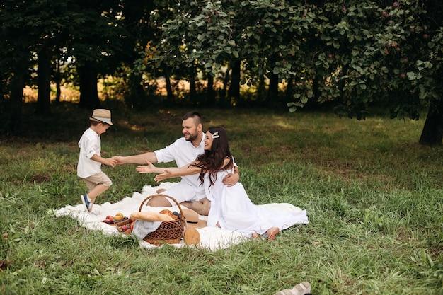 Famiglia felice che fa un picnic all'aperto con il loro figlio carino