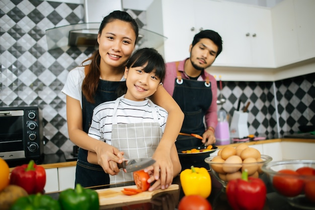 Happy family help cooking meal together in kitchen at home.