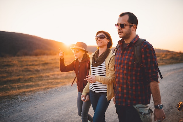 Happy family hiking on a dirt road during sunset