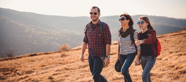 幸せな家族が山で一緒にハイキング