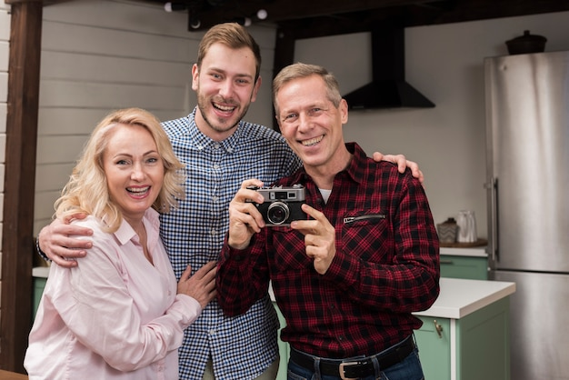 Happy family holding camera in the kitchen