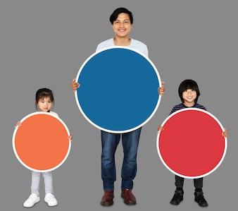 カラフルなラウンドボードを持って幸せな家族