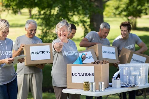 Счастливая семья держит пожертвования коробки с пальца вверх