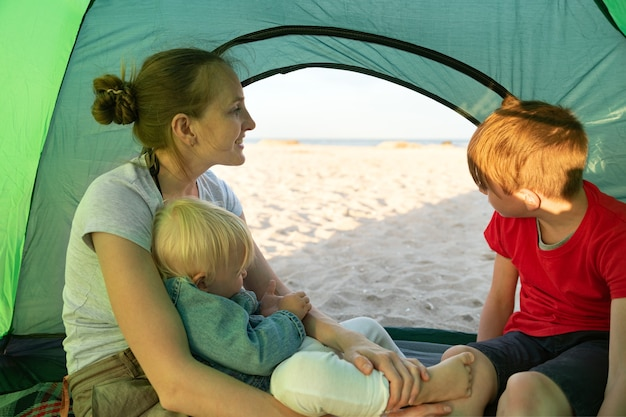 자연 속에서 자녀와 함께 텐트에서 행복한 가족 휴가.