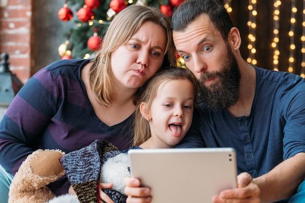 幸せな家族の休日。愛する両親とかわいい娘が楽しんで、顔を引っ張って、タブレットカメラで自分撮りをしています。