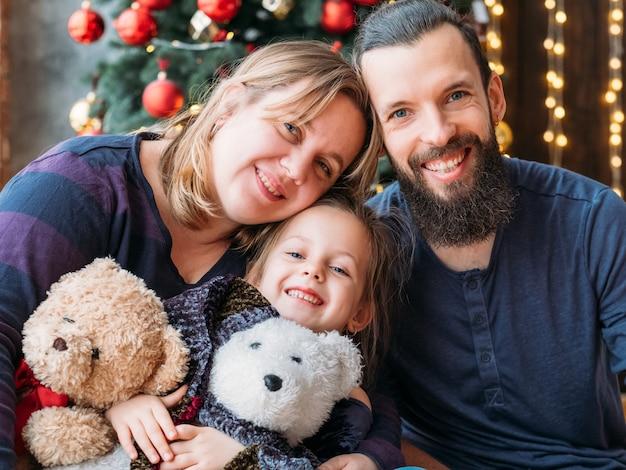 幸せな家族の休日。テディベアと愛情のある両親とそのかわいい小さな娘の肖像画。