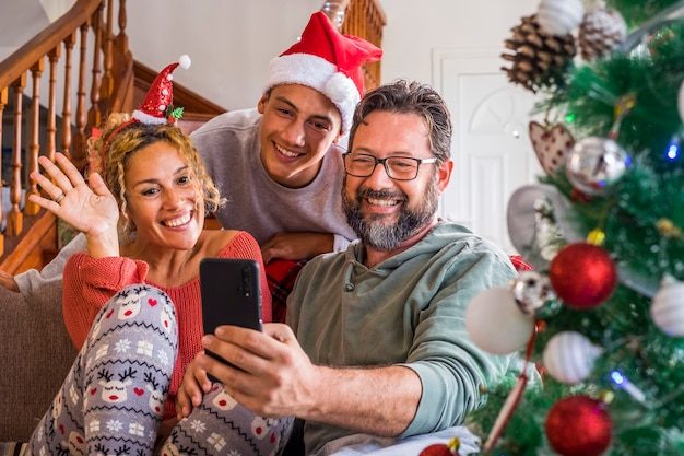 Happy family at home during christmas eve day enjoy a video phone call with friends and parents