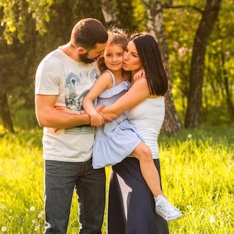 Счастливая семья обнимает в парке