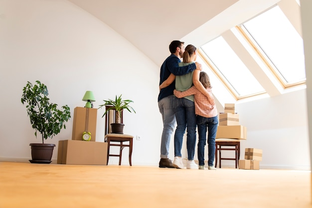 Happy family hugging together and standing in living room in the new house