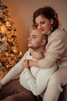 幸せな家族の夫と妻は、クリスマスツリーの近くのベッドで家で抱き合っています。