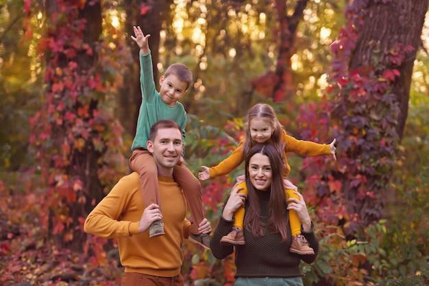 Счастливая семья, муж, жена, малыш: мальчик и девочка играют на улице осенью