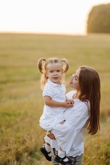 秋の畑で幸せな家族。母、父、赤ちゃんは夕日の光線で自然の中で遊ぶ
