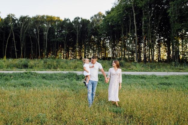 Счастливая семья в парке летом осенью. мать, отец и ребенок играют на природе в лучах заката
