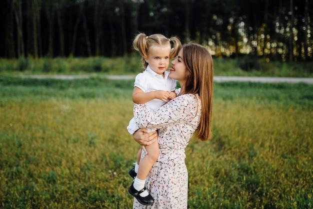 夏の秋の公園で幸せな家族。母、父、赤ちゃんは夕日の光線で自然の中で遊ぶ