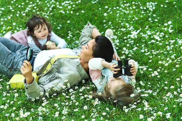 Счастливая семья в парке. мать и ее две дочери, лежащие в поле ромашки.