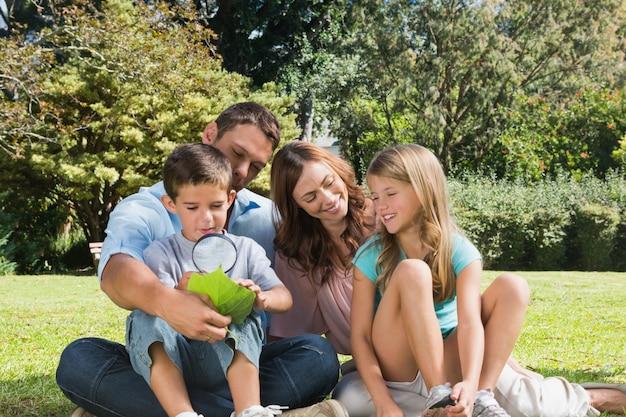 돋보기와 잎을 검사하는 아버지와 아들과 함께 공원에서 행복한 가족