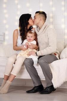 ベッドで遊んだりキスしたりする幸せな家族